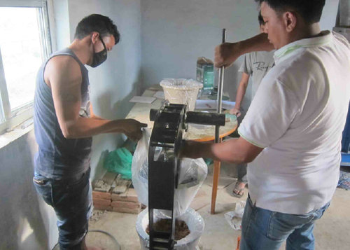 Pressing filters with the Potters for Peace portable press - Ceramic Water Filter Solutions